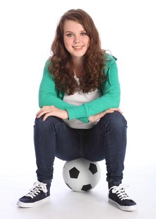 Cheerful teenage girl soccer player sitting on a football relaxing wearing green hoodie and blue jeans. Zdjęcie Seryjne