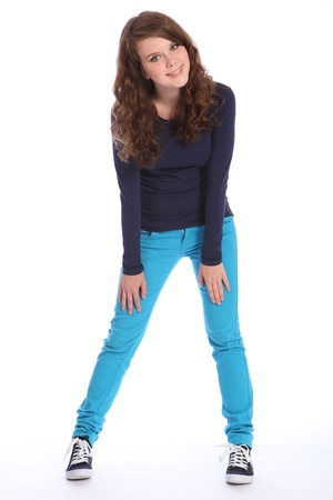 High school student: Beautiful teenager girl with bright blue eyes has fun in studio standing wearing blue jeans and navy long sleeved top and blue trainers. She has long brown hair. Stock Photo
