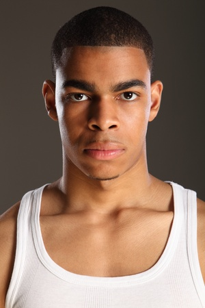 young man portrait: Good looking young African American man wearing white vest and a serious expression on his handsome face. Shot against a grey backdrop.