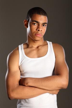 Cuerpo tonificada y ajuste de buen aspecto joven afroamericano hombre vistiendo chaleco blanco, de brazos cruzados y una expresi�n seria en su rostro hermoso. Dispar� contra un tel�n de fondo gris.