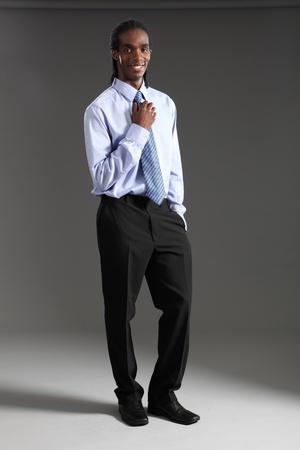 dreadlocks: Apuesto joven empresario afroamericano permanente vistiendo negro traje pantalón y camisa azul y corbata de cuello. Él tiene cortos rastas y una sonrisa feliz.