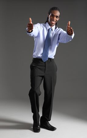 Thumbs up in success sign for handsome young African American businessman standing wearing black suit trousers and blue shirt and neck tie. He has short dreadlocks and a big happy smile. photo
