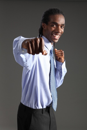 Fun fighting punch from handsome young African American businessman standing wearing black suit trousers and blue shirt and neck tie. He has short dreadlocks and a big happy smile. photo