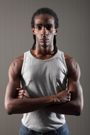 dreadlocks: Músculos de los hombros y bíceps en la dura y joven afroamericano con rastas cortas, el uso de chaleco gris con los brazos cruzados. Tiene una expresión seria en su cara de miedo.