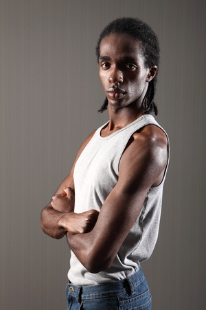 scowl: Shoulder and bicep muscles on tough young African American man with short dreadlocks, wearing grey vest with arms folded. He has a serious scary expression on his face. Stock Photo
