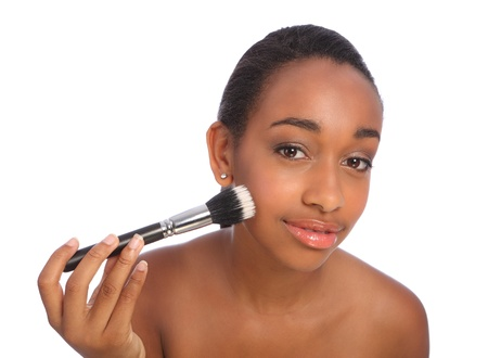 Beautiful young african american woman applying make up using stippling brush also referred to as a cosmetics powder brush. Stock Photo - 10526743