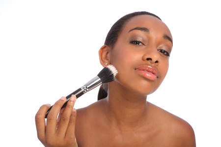 flawless: Flawless skin care for a beautiful young african american woman applying make up using stippling brush also referred to as a cosmetics powder brush. Stock Photo