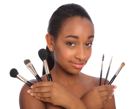 make up brushes: Beautiful young African American beautician woman holding set of six make up brushes. Brush types are powder blusher foundation or base, eye lash separator, brow eye shadow and eye liner brush. Stock Photo