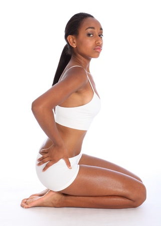 sitting on floor: Profile view of a beautiful healthy young african american woman wearing white sports underwear showing off fit body, sitting on floor bare foot. Stock Photo