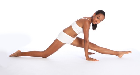 Beautiful young athletic African American fitness woman wearing sports underwear, having fun doing warm up leg stretch on the floor with big happy smile. photo