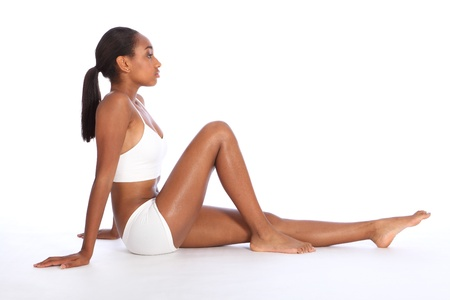 Healthy fit body of beautiful young black African American woman sitting on the floor, wearing white sports underwear and bare foot. Taken on white background. Stock Photo - 10526735