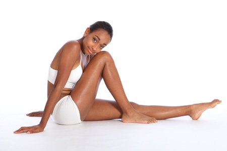 Healthy fit body of beautiful young black African American woman sitting on the floor, wearing white sports underwear and bare foot. Taken on white background. photo