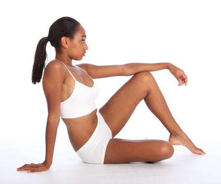 jungen unterwäsche: Gesunde fit Körper der schönen jungen schwarzen African American Frau sitzt auf dem Boden, trägt weiße Sport Unterwäsche und barfuß. Taken auf weißem Hintergrund. Lizenzfreie Bilder