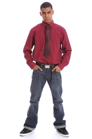 Smartly dressed good looking young African American teenage student boy standing with serious expression on his handsome face wearing casual jeans and formal long sleeved shirt and necktie. photo