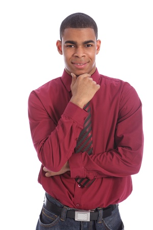 deep thought: Smartly dressed good looking young African American teenage student boy standing with happy expression on his handsome face, hand on chin deep in thought, wearing long sleeved shirt and necktie.