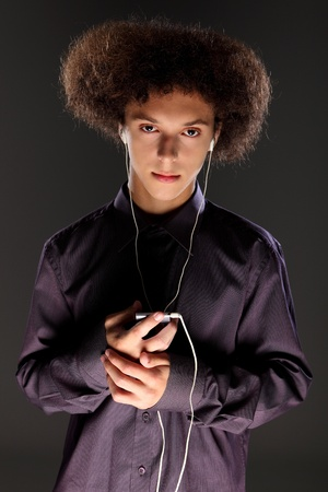 bushy: Teenager boy with big bushy afro hair style wearing white ear plugs listening to music on his cell phone. Has serious staring expression and wearing a purple button shirt.