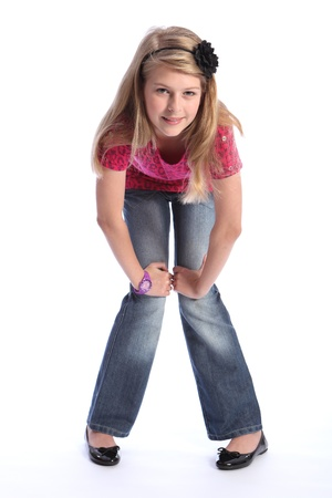 bending over: Pretty caucasian school girl with long blonde hair wearing blue denim jeans and a pink t-shirt. She is standing and leaning forward looking down into camera.