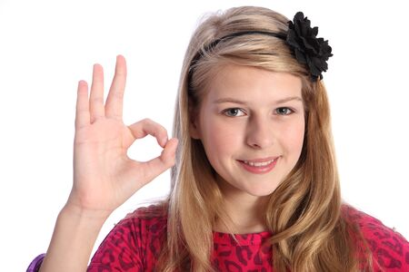 hair band: Fun positive okay hand sign by pretty caucasian school girl with happy smile, wearing pink t-shirt with black flower hair band in her blonde hair.
