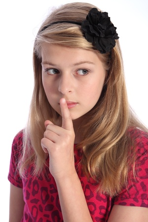 hair band: Frightened look of worry from school girl child with one finger over her mouth indicating silence or to keep quiet. Girl has long blonde hair and blue eyes.