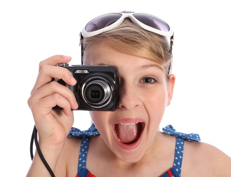 Excited pretty blonde teenager photographer girl with big smile having fun taking pictures with a compact camera held up to her blue eye and sunglasses on her head. photo