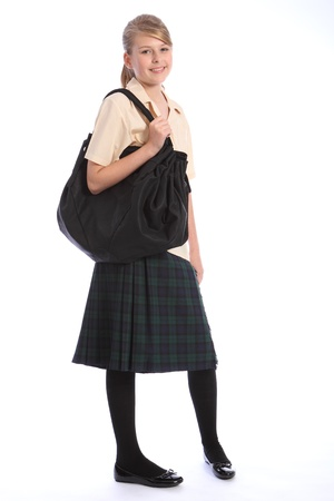 Teenage girl smiles wearing secondary school student uniform of tartan skirt and beige shirt, with big black shoulder bag. Stock Photo