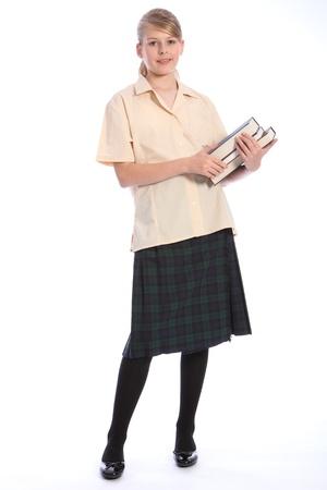 Ni�a de la escuela secundaria los estudiantes adolescentes con uniforme escolar formal de falda escocesa y una camisa beige, mantener los libros en sus brazos. Foto de archivo - 10561124