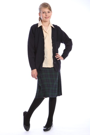 Smile from beautiful teenage high school student girl wearing school uniform, tartan skirt and beige shirt with navy cardigan, holding on to her bag. photo