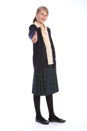 Thumbs up success with a smile from beautiful teenage high school student girl wearing school uniform, tartan skirt and beige shirt with navy cardigan. photo