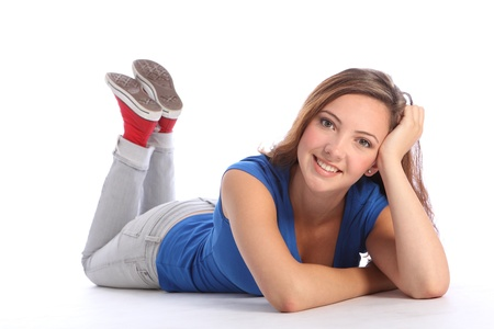 lying down: Beautiful young teenager school girl 16, with long brown hair wearing blue t-shirt and denim jeans, lying on the floor with a big smile. Stock Photo