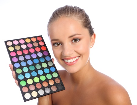 Beautiful young make up artist woman with brilliant smile holding an eyeshadow colour 60 palette, taken against white background. Stock Photo - 10572528