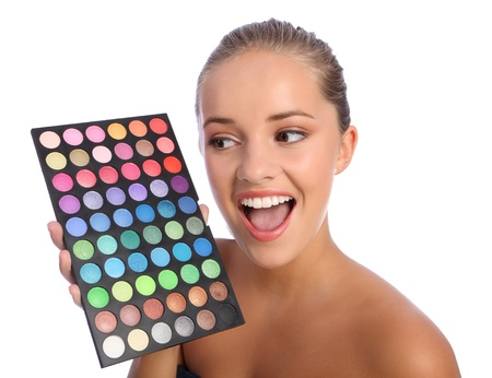 Excited beautiful young make up artist woman with brilliant smile holding an eyeshadow colour 60 palette, taken against white background. Stock Photo - 10572530