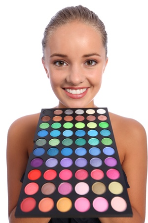 Beautiful young make up artist girl with happy smile holding an eyeshadow colour 60 palette below her chin, taken against white background. photo