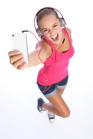 shorts: Feliz chica adolescente que llevaba pantalones cortos de mezclilla y top rosa, mirando cantar y divertirse escuchando m�sica en su tel�fono celular.