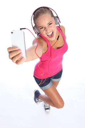 Happy teenage girl wearing denim shorts and pink top, looking up singing and having fun listening to music on her cell phone. photo