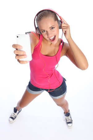 Dancing to music on her cell phone a teenage girl wearing denim shorts and pink top looks up singing with big happy excited expression. photo