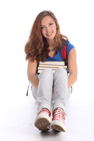 Study time for beautiful high school teenage student girl holding education books sitting on floor, with long brown hair wearing blue t-shirt, jeans and red sneakers and red school backpack. Stock Photo - 10572524