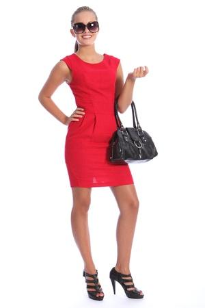 Mujer hermosa moda joven sexy modelo, vistiendo Zapatos negros de tac�n y un corto vestido rojo con bolso negro. Tiene el cabello rubio se retir� llevaba gafas de sol. Foto de archivo