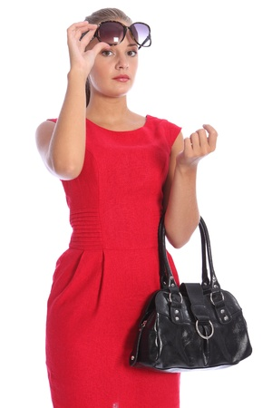 snob: Beautiful sexy young fashion model woman, wearing a red dress with black handbag. She has blond hair pulled back wearing sunglasses.
