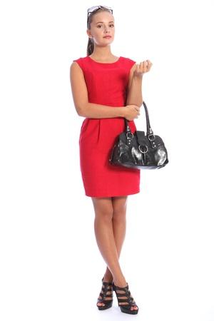 Hermosa joven sexy modelo de moda en un corto vestido rojo con bolso negro, retirado el pelo rubio y gafas de sol de cabeza.