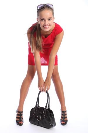 블랙 높은 굽 구두와 그녀의 검은 핸드백에 절곡 짧은 빨간 드레스를 입고 사랑스러운 행복한 미소와 아름 다운 섹시 한 젊은 패션 모델 여자. 그녀는 갈색 머리와 선글라스 금발있다.