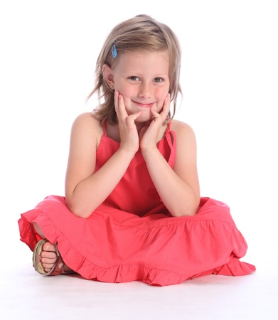 Cute blonde six year old primary school girl wearing coral pink dress sitting cross legged on floor with a happy smile. Stock Photo
