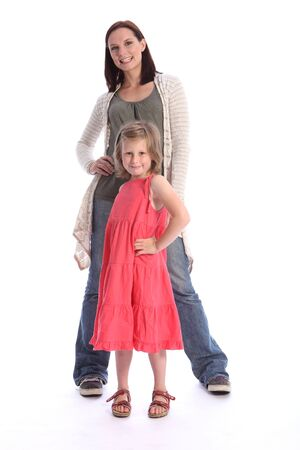 Family love of mother and daughter having fun posing together in studio. Girl is six years old wearing coral red dress while mother wearing blue jeans and long cardigan. photo