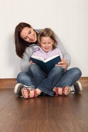 Education at home for young primary school girl with mother teaching her to read a book. Both wearing denim jeans and hoodies sitting cross legged on the floor. photo