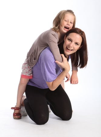 Family fun as mother gives daughter a piggy back ride. Child is wearing a grey cardigan her mum has on a bright purple shirt and black leggings. photo