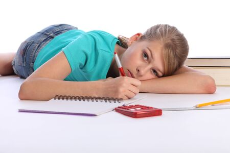 Young blonde primary school girl lying on floor doing math homework, writing with pen and calculator nearby. She is wearing a blue t-shirt and denim shorts looking tired. photo