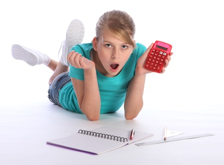 Young blonde primary school girl lying on floor doing math education homework, holding up red calcuator with big surprised expression on her face. photo