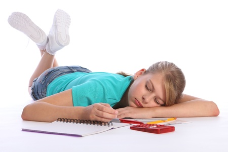 Tired blonde primary school girl lying on floor falls asleep doing math education homework, still holding red pen with book and calculator nearby. photo