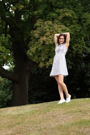 happy moment: Happy moment enjoying nature for slim young woman wearing short dress outdoors in countryside with arms outstretched, enjoying sunshine near large forest trees.