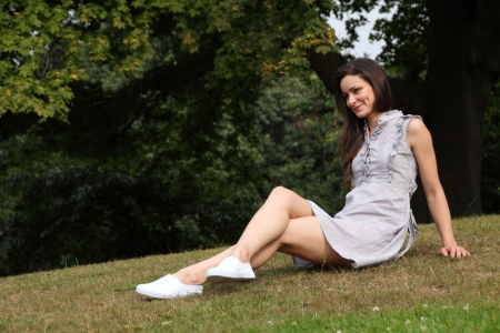 Long legged young girl wearing short summer dress sitting on the grass in the park. Deep green forest trees behind her. Stock Photo - 10685144