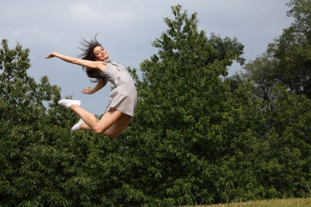 woman floating: Fun high flying success and joy for happy slim young woman wearing short dress, jumping into the air outdoors in countryside, enjoying summer sunshine in the park. Stock Photo